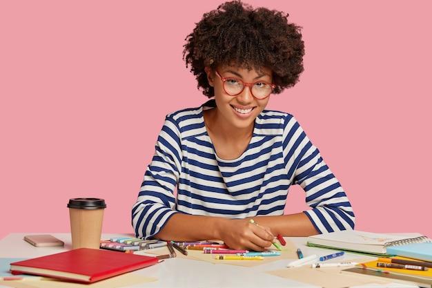 Foto horizontal de um multiplicador de aparência agradável com corte de cabelo afro, usa giz de cera, gosta de bebida quente