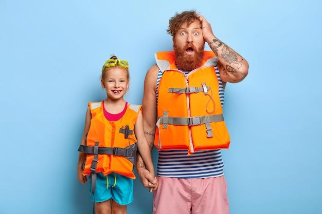Foto horizontal de um pai ruivo barbudo espantado com um colete salva-vidas inflado laranja