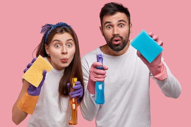 Foto horizontal de um rapaz bonito surpreso e uma mulher atraente segurando esponjas na frente, carregando detergentes e limpando janelas na cozinha