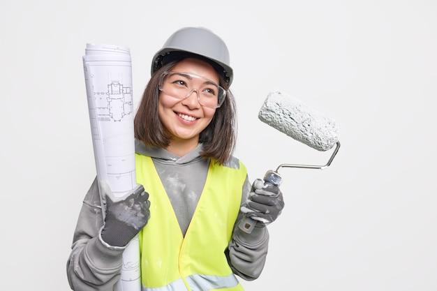 Foto horizontal de um sorriso positivo de uma trabalhadora da construção civil segura positivamente o rolo de pintura e a planta, estando de bom humor, prontos para começar a trabalhar