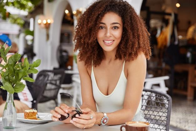 Foto horizontal de uma adorável modelo feminina de pele escura com penteado afro encaracolado, aproveitando o tempo de recreação durante o fim de semana, posa diante do interior aconchegante do café