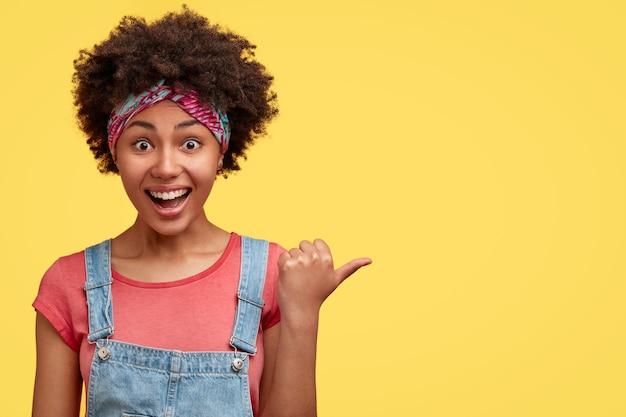Foto horizontal de uma alegre mulher afro-americana, encaracolada e morena, com uma expressão radiante, apontando para a parede amarela, vestindo um macacão da moda