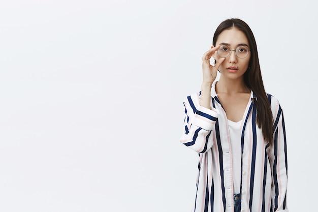 Foto horizontal de uma atraente mulher asiática natural com pele bronzeada e longos cabelos escuros, tocando os óculos redondos nos olhos, vestindo uma elegante camisa listrada sobre uma camiseta branca, olhando um sonho