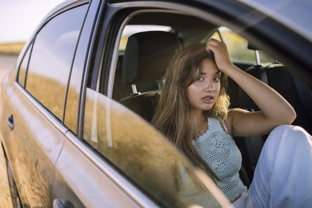 Foto horizontal de uma bela jovem caucasiana posando no banco da frente de um carro em um campo