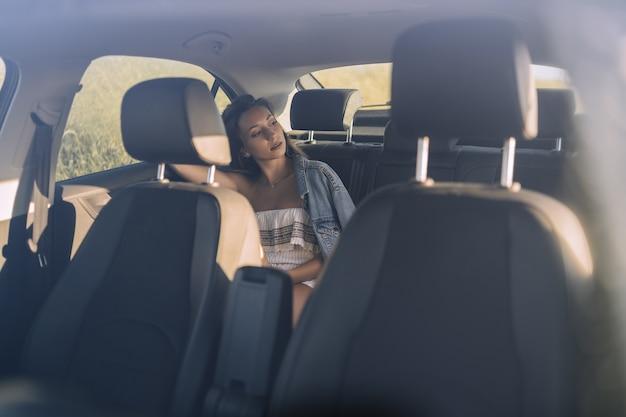 Foto horizontal de uma bela jovem caucasiana posando no banco de trás de um carro em um campo