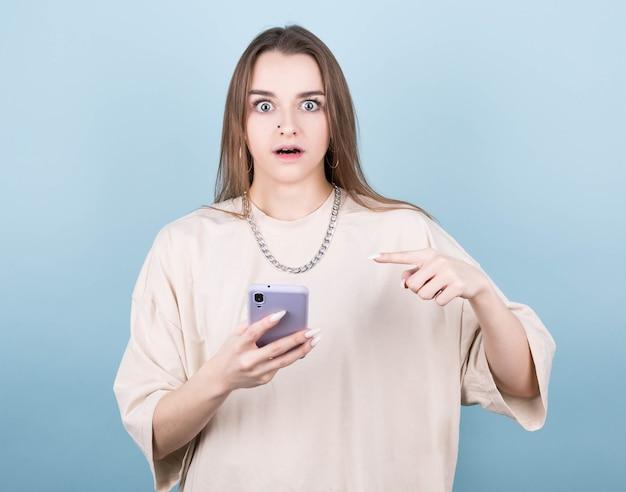 Foto horizontal de uma bela jovem com cabelo comprido parece com olhos atentos, segura um smartphone moderno