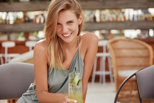 Foto horizontal de uma bela jovem loira vestida com roupas casuais, recriada contra o interior de um café aconchegante com um coquetel frio fresco, sorri feliz