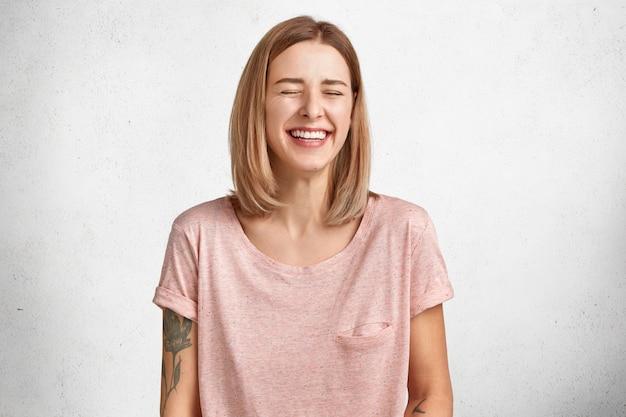 Foto horizontal de uma bela jovem rindo com alegria, mantém os olhos fechados, não consegue parar os sentimentos, mostra dentes brancos perfeitos e uniformes