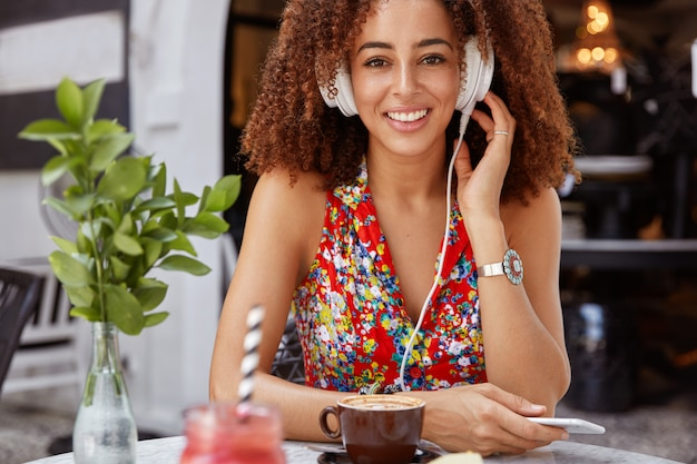 Foto horizontal de uma bela melomana de pele escura segurando um celular moderno, curtindo ouvir música