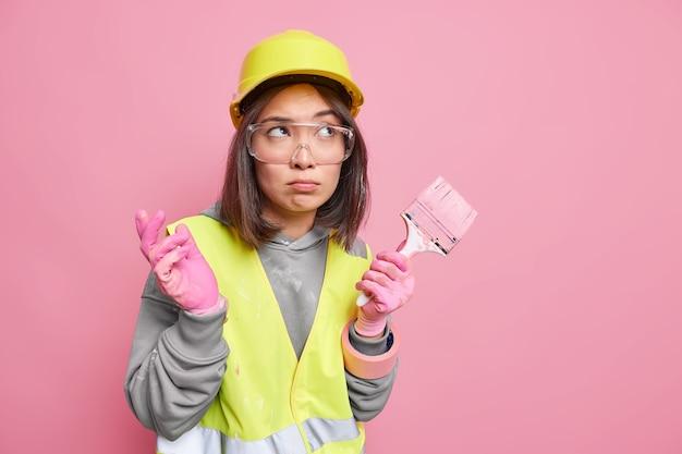 Foto horizontal de uma construtora pensativa, vestida de uniforme, segura o pincel, mergulhando em pensamentos, usa um capacete de proteção e uma jaqueta refletiva