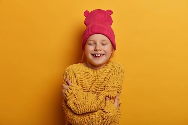 Foto horizontal de uma criança feliz do sexo feminino se abraçando, sentindo-se aconchegante, usando chapéu rosa e suéter de tricô, estando em alto astral, isolado sobre a parede amarela. filhos, auto estima