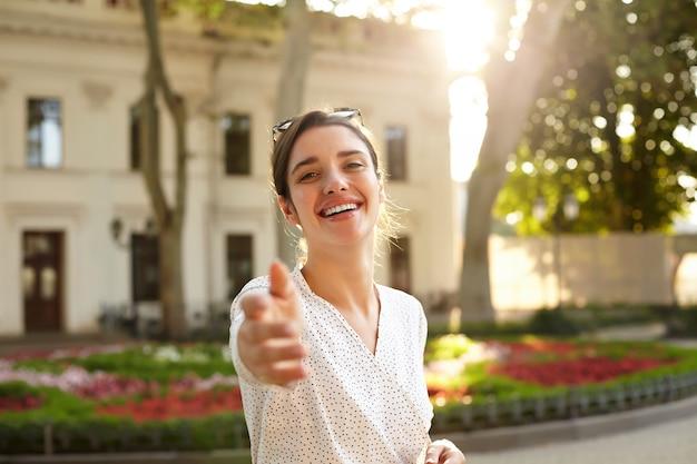 Foto horizontal de uma encantadora jovem morena com um vestido branco romântico, parecendo feliz e sorrindo amplamente, levantando a mão em um gesto de siga-me