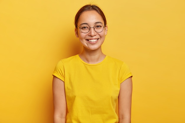 Foto horizontal de uma estudante asiática feliz usando grandes óculos redondos, casual wear amarelo, sorri suavemente, satisfeita após um dia de sucesso na universidade, vestida com uma camiseta amarela de verão