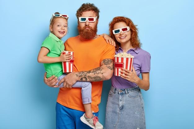 Foto horizontal de uma família feliz de gengibre, passando o tempo livre no cinema, venha para a estreia do filme, coma pipoca salgada. pai barbudo carrega filha nas mãos, mãe alegre em óculos 3d perto