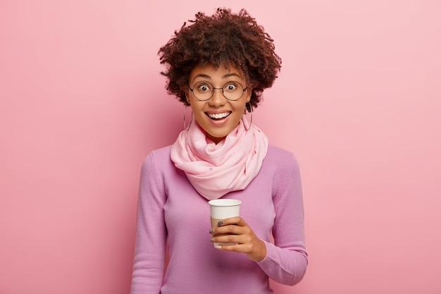 Foto horizontal de uma feliz mulher de pele escura com penteado afro, segurando um copo de papel com café, vestindo um macacão roxo e um lenço de seda