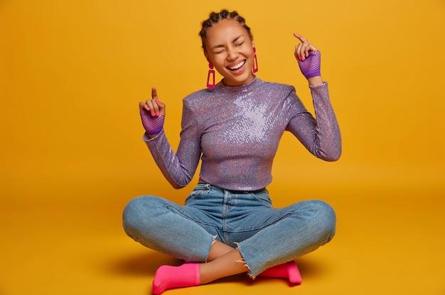 Foto horizontal de uma garota de pele escura divertida e despreocupada sentada com as pernas cruzadas e rindo, levanta os braços, tem reunião em grupo, ouve algo muito engraçado, fecha os olhos de positividade, isolado na parede amarela