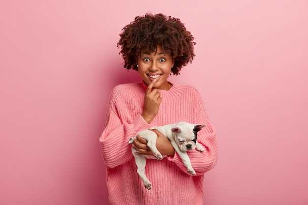 Foto horizontal de uma garota de pele escura encantada com corte de cabelo encaracolado, tem uma expressão curiosa e alegre, mantém o dedo nos lábios, segura o cachorrinho sonolento, modelos sobre uma parede rosada. amizade e animais