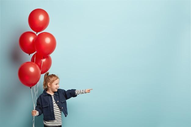 Foto horizontal de uma garota feliz com roupas elegantes, apontando para a distância, comemorando aniversário
