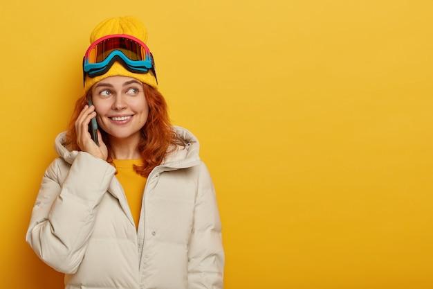 Foto horizontal de uma garota muito sorridente, esquiadora, chama parentes com smartphone, fala sobre suas férias de inverno e usa óculos de snowboard