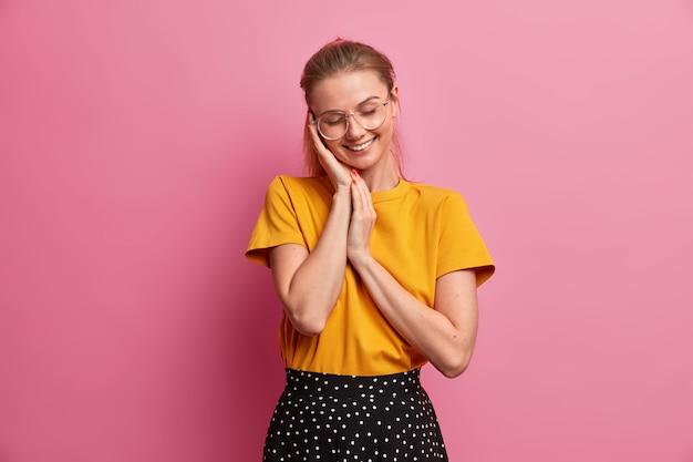 Foto horizontal de uma garota muito sorridente mantendo as mãos perto do rosto fechando os olhos de prazer