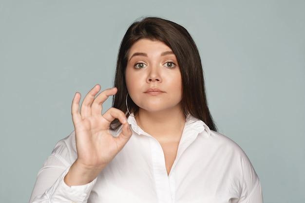 Foto horizontal de uma gerente feminina gorducha séria e confiante, vestida com uma camisa formal branca, conectando o indicador e o polegar na frente, fazendo um gesto de ok, mostrando que tudo está sob controle