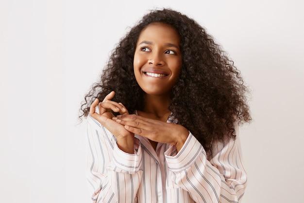 Foto horizontal de uma jovem afro-americana bonita em uma camisola elegante, olhando para cima com uma expressão facial pensativa e animada, mordendo o lábio e esfregando as mãos, tendo uma ideia ou um plano brilhante, sonhando
