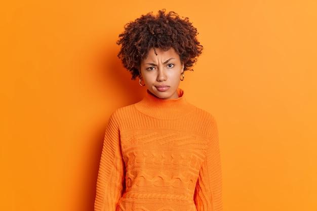 Foto horizontal de uma jovem afro-americana descontente com o rosto franzido e olhando com raiva para a câmera