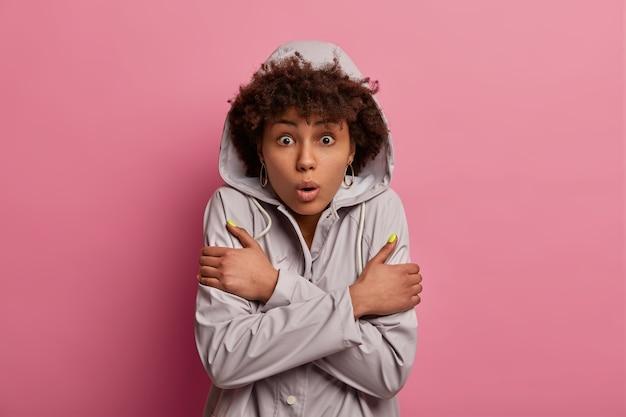 Foto horizontal de uma jovem afro-americana em choque cruzando os braços, usando um anoraque com um casaco de capuz, sentindo-se assustada, com frio e tremendo de medo, medo de algo, poses sobre uma parede rosa