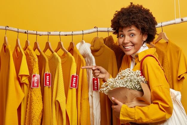 Foto horizontal de uma jovem afro-americana encantada aponta para roupas elegantes à venda penduradas nos trilhos, carrega uma bolsa e um lindo buquê, tem um sorriso cheio de dentes, isolado sobre um fundo amarelo