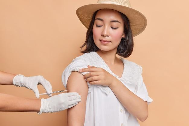 Foto horizontal de uma jovem asiática morena sendo inoculada no ombro, usando chapéu de feltro e vestido branco
