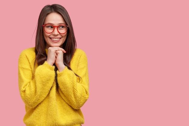 Foto horizontal de uma jovem bonita com as mãos embaixo do queixo, sorrindo alegremente, em alto astral, curtindo bons momentos, usando roupas largas amarelas, óculos de aro vermelho