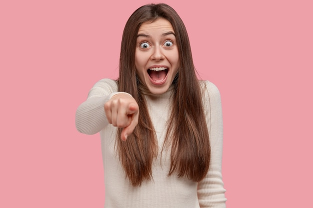 Foto horizontal de uma jovem bonita e positiva aponta diretamente para a câmera com o dedo indicador, mantém a boca bem aberta e usa roupas casuais