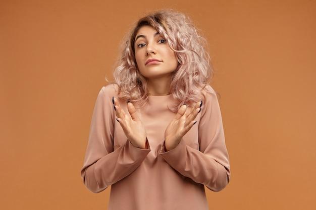Foto horizontal de uma jovem caucasiana confusa e intrigada com piercing facial, levantando as sobrancelhas e encolhendo os ombros, perdida, hesitando, os olhos cheios de dúvidas