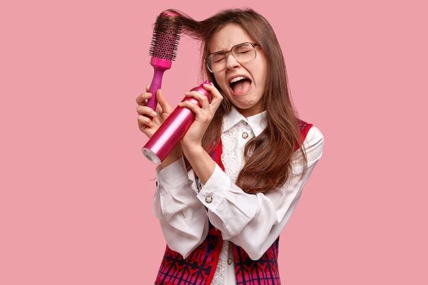 Foto horizontal de uma jovem deprimida e descontente chora desesperadamente enquanto segura o spray de cabelo perto da boca e penteia o cabelo com uma escova de cabelo