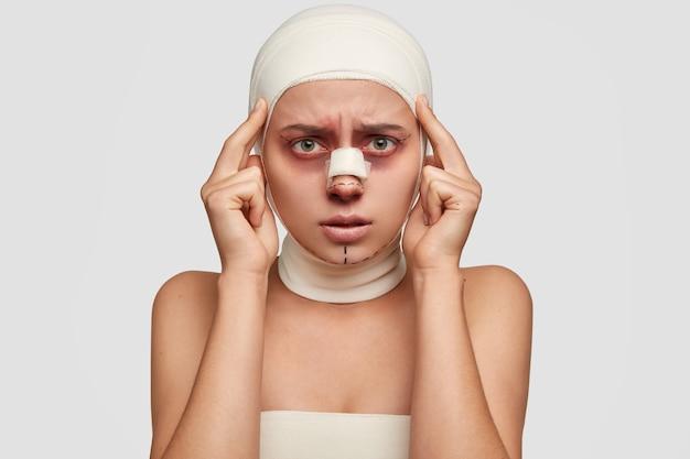 Foto horizontal de uma jovem europeia descontente com hematomas na pele ao redor dos olhos e dor de cabeça