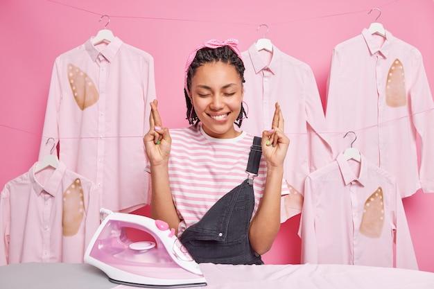 Foto horizontal de uma jovem feliz empregada doméstica afro-americana com dreadlocks perto da tábua de passar com os dedos cruzados acredita que os sonhos se tornem realidade.