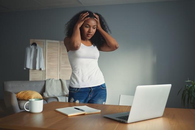 Foto horizontal de uma jovem freelancer afro-americana desesperada de mãos dadas na cabeça, sentindo-se estressada e em pânico por causa do prazo ou de um problema no computador, em pé na mesa com o laptop aberto