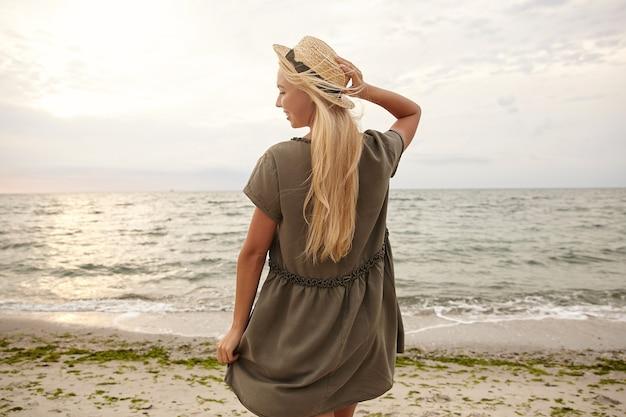 Foto horizontal de uma jovem loira de cabelos compridos encantadora, mantendo a mão levantada em seu chapéu de barco e sorrindo alegremente enquanto posava de costas à beira-mar