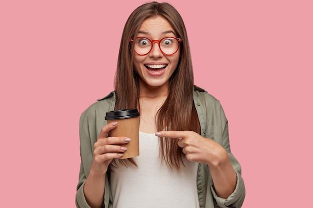 Foto horizontal de uma jovem morena alegre aponta para um café para viagem, tem uma expressão alegre, anuncia uma bebida aromática,