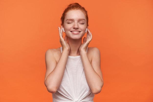 Foto horizontal de uma jovem mulher atraente com cabelo ruivo, vestindo roupas casuais em nó, curtindo sua música favorita com os olhos fechados e mantendo as mãos nos fones de ouvido, isolado sobre fundo laranja