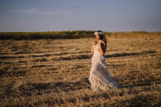 Foto horizontal de uma jovem mulher branca com um vestido branco, posando em um campo