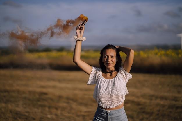 Foto horizontal de uma jovem mulher branca posando com uma bomba de fumaça em um campo