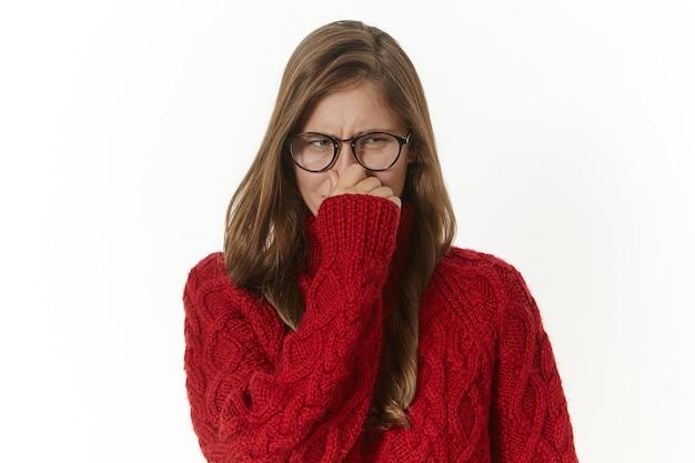 Foto horizontal de uma jovem mulher descontente e enojada usando óculos e suéter, fazendo uma careta e beliscando o nariz por causa do mau cheiro corporal, comida estragada, meias sujas ou axilas suadas e fedorentas