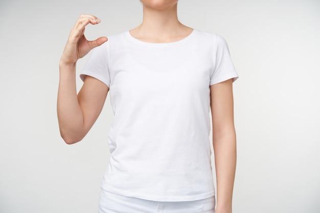 Foto horizontal de uma jovem mulher vestida com roupas casuais, levantando a mão e formando com os dedos a letra c usando a linguagem de sinais, isolada sobre fundo branco