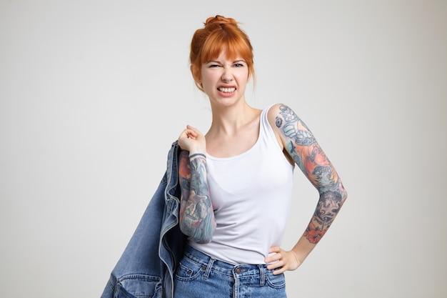 Foto horizontal de uma jovem ruiva com tatuagens segurando o casaco jeans com a mão levantada e franzindo a testa enquanto olha para a câmera, isolada sobre fundo branco