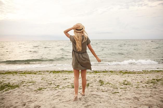 Foto horizontal de uma jovem senhora de cabelos longos e cabelos brancos, mantendo seu chapéu de barco com a mão levantada, enquanto olha para o mar e em pé de costas para a costa