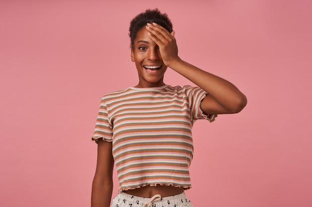 Foto horizontal de uma jovem senhora de olhos castanhos e cacheados levantando emocionalmente a mão ao rosto enquanto sorri alegremente na frente, de pé sobre a parede rosa