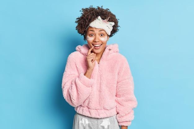 Foto horizontal de uma linda mulher afro-americana alegre com expressão facial positiva, vestida com um pijama macio ouve boas notícias de manhã isolada sobre a parede azul