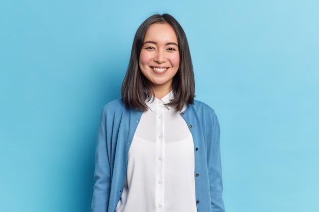Foto horizontal de uma linda mulher asiática com cabelos escuros sorrindo agradavelmente olhando diretamente, tem um sorriso cheio de dentes, usa camisa branca e macacão
