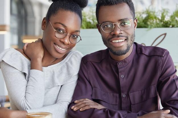 Foto horizontal de uma linda mulher de pele escura com expressão alegre, feliz por conhecer seu melhor amigo afro-americano, sentada em um café ao ar livre